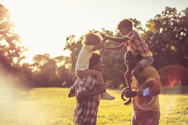 siblings on parents shoulders