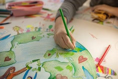 Close up of child's hands while drawing Ecofriendly theme on paper.