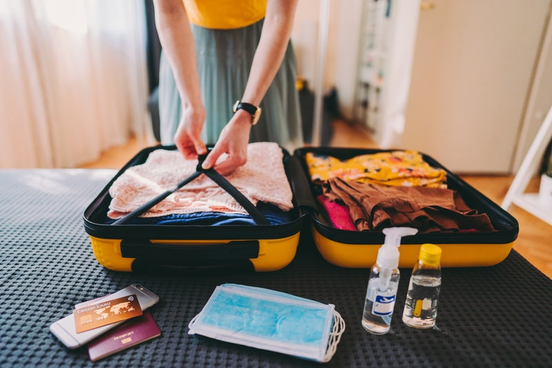 Woman packing suitcase for business travel including face masks and airplane travel-sized antibacterial hand gels