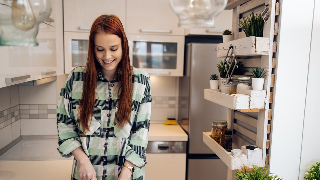 A woman wearing a green flannel cuts up vegetables in her kitchen.