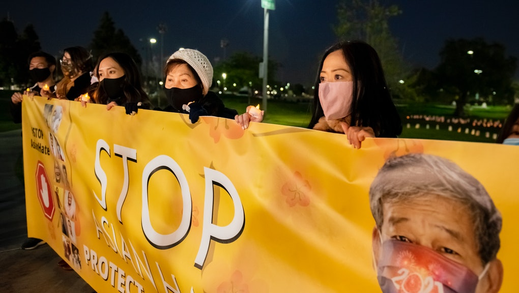 FOUNTAIN VALLEY, CA - MARCH 04: Linda Nguyen, right, a victim of anti-Asian attacks, joins members of the Vietnamese community and others hold up a banner against Asian hate during a gathering at Fountain Valley Sports Park in Mile Square Park in Fountain Valley on Thursday, March 4, 2021 to commemorate the one year of the coronavirus pandemic and honor those who have died and to bring attention to the growing number of anti-Asian hate crimes where Asian Americans have been subject to hate because they have been linked to bringing the virus. (Photo by Leonard Ortiz/MediaNews Group/Orange County Register via Getty Images)