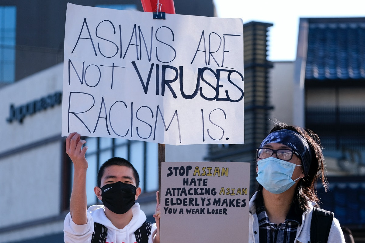 """Demonstrators wearing face masks and holding signs take part in a rally """"Love Our Communities: Build Collective Power"""" to raise awareness of anti-Asian violence, at the Japanese American National Museum in Little Tokyo in Los Angeles, California, on March 13, 2021. - Reports of attacks, primarily against Asian-American elders, have spiked in recent months -- fuelled, activists believe, by talk of the """"Chinese virus"""" by former president Donald Trump and others. (Photo by RINGO CHIU / AFP) (Photo by RINGO CHIU/AFP via Getty Images)"""