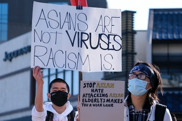 """Demonstrators wearing face masks and holding signs take part in a rally """"Love Our Communities: Build..."""
