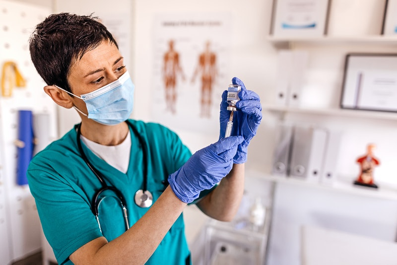 A medical professional prepares a syringe for vaccination. The underlying conditions that qualify pe...