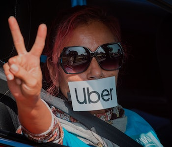 A protester gestures as Uber and Lyft drivers drive through Beverly Hills on their way to demonstrat...