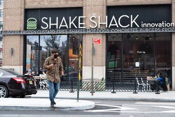 A man walking near a Shake Shack