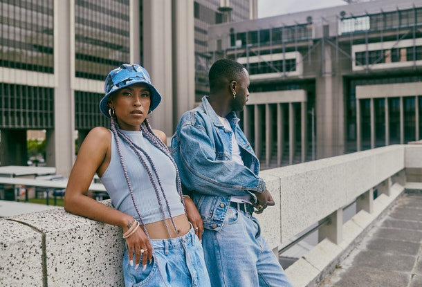 Shot of a trendy young couple leaning against a wall in the city