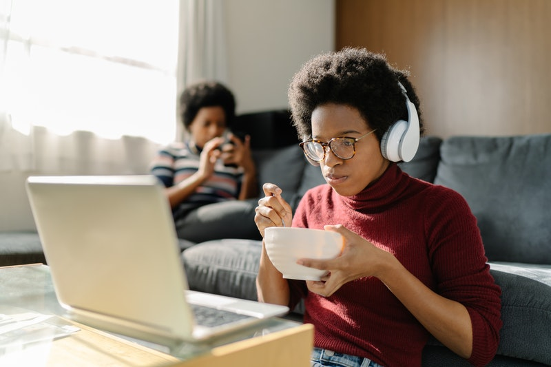 Two Black women are spending their time using a laptop and a smart phone comfortably at home.