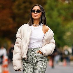 PARIS, FRANCE - SEPTEMBER 25: Aimee Song wears sunglasses, a white puffer jacket, a white sleeveless...