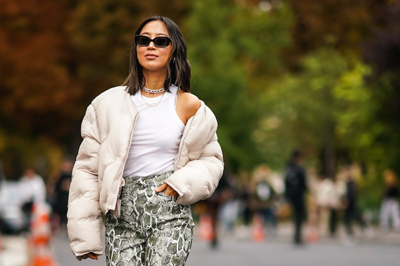 PARIS, FRANCE - SEPTEMBER 25: Aimee Song wears sunglasses, a white puffer jacket, a white sleeveless tank top, snake print pants, a chain metallic necklace, outside Margiela, during Paris Fashion Week - Womenswear Spring Summer 2020, on September 25, 2019 in Paris, France. (Photo by Edward Berthelot/Getty Images)