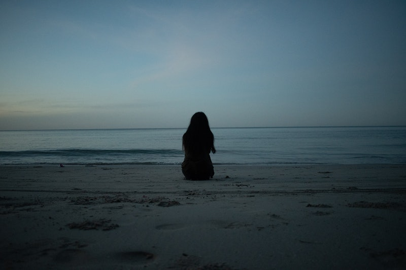 A woman sits and looks at the sunrise. Trauma can cause deep damage to the brain.