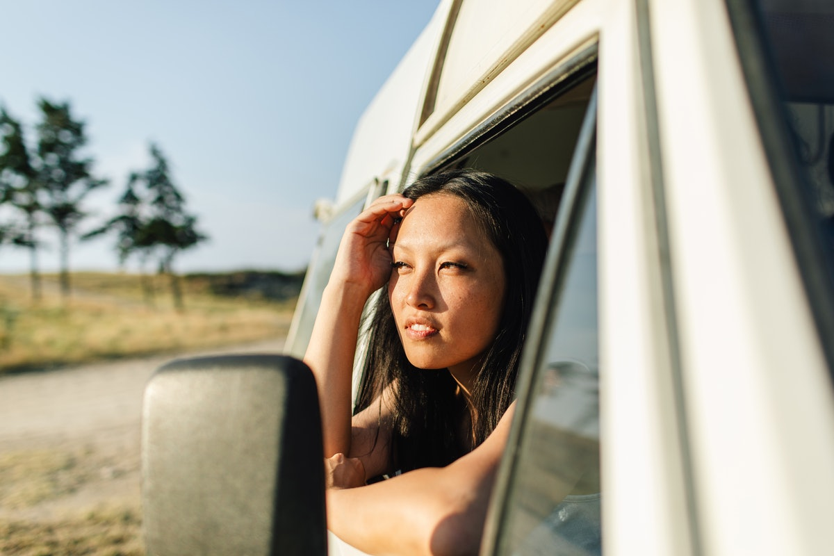 Photo of young woman on a summer road trip with a van vehicle