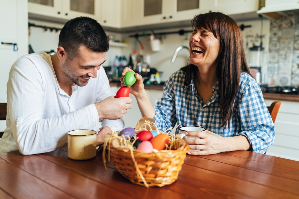 Happy siblings playing with Easter eggs and laughing.
