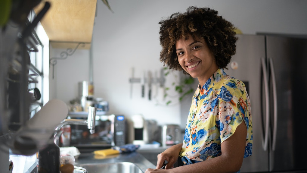 A happy woman chops a vegetable in her kitchen.