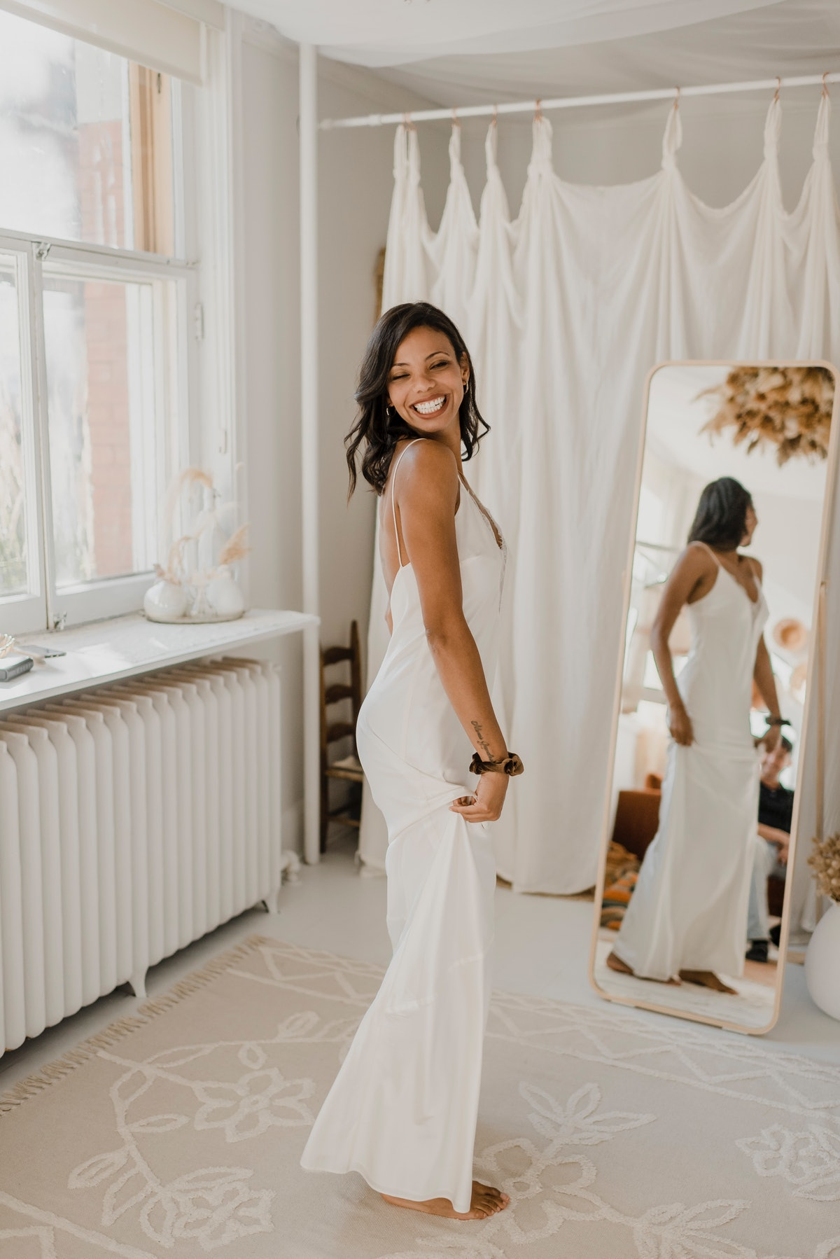 A bride smiles after saying yes to the dress, and standing in the view of a full-length mirror.
