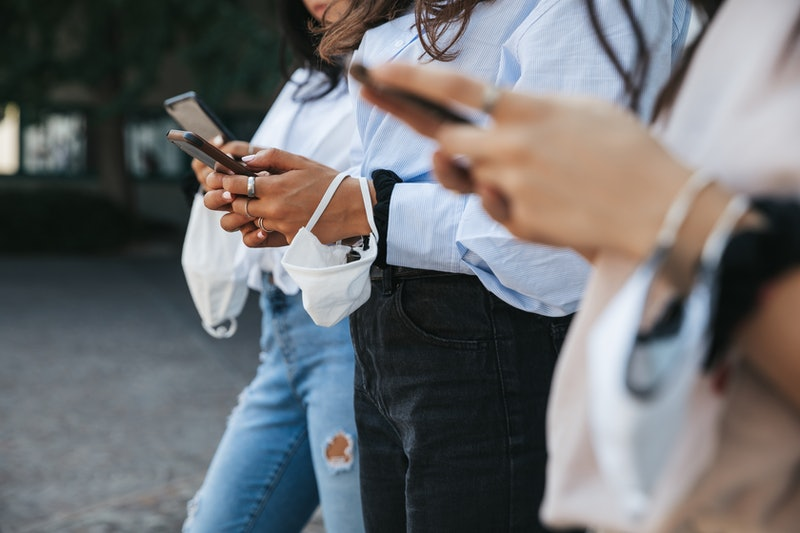 Three people stand outside in a line, all texting on their phones. Figuring out what texts to send a family member with anxiety can be anxiety-inducing on its own, but these therapist-approved texts can help.