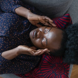 A woman lies on a couch with an allergy-induced headache.