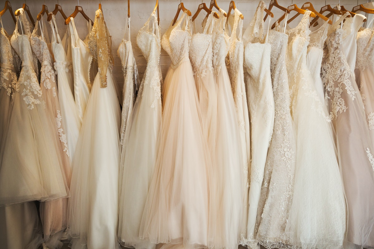 Several wedding dresses with appliqué, lace, and floral detailing are displayed on a rack.