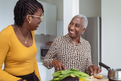 A beautiful black senior woman is cooking with her granddaughter. They are enjoying the special bonding time together as the grandmother slices vegetables.