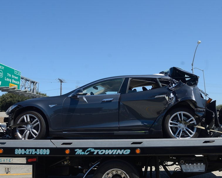 SEAL BEACH, CA - AUGUST 15: A damaged Tesla sits on a tow truck after a collision in the HOV lane on...
