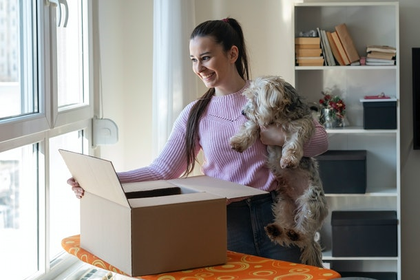 A young woman opens a dog subscription box while holding her fluffy dog.