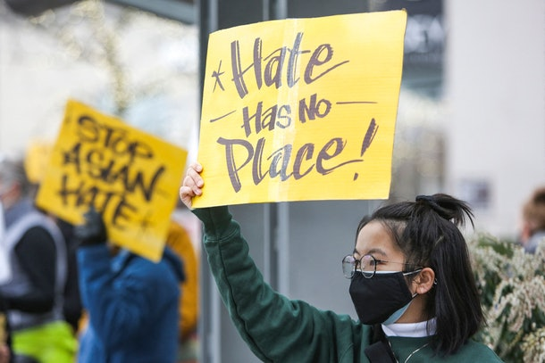 """A University of Washington student, who wished to remain anonymous, holds a sign that reads """"hate has no place"""" during the We Are Not Silent rally organized by the Asian American Pacific Islander (AAPI) Coalition Against Hate and Bias in Bellevue, Washington on March 18, 2021. - The shooting rampage in Atlanta by a 21-year-old white man that left six women of Asian origin dead has laid bare the fears of an Asian-American community on edge over a spike in hate crimes because of the coronavirus pandemic. (Photo by Jason Redmond / AFP) (Photo by JASON REDMOND/AFP via Getty Images)"""