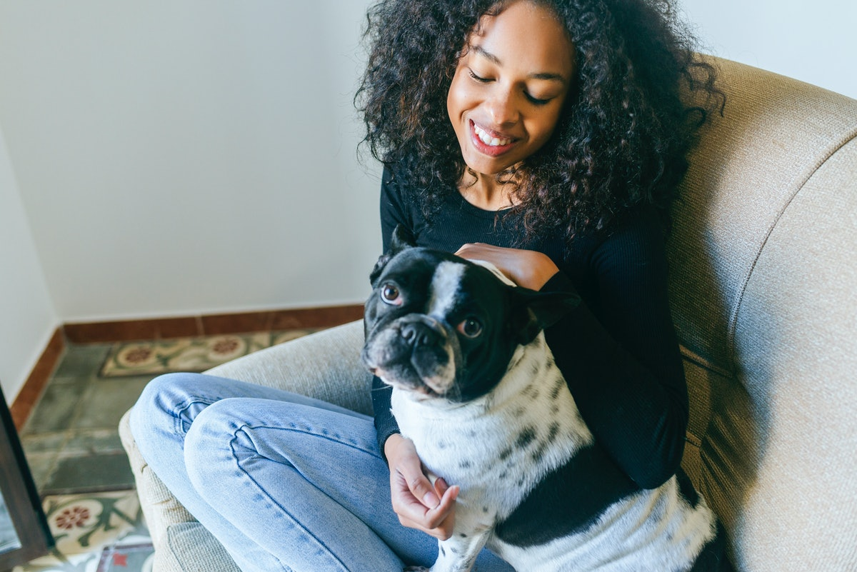 A young woman sits with her dog and waits for a dog subscription box to arrive.