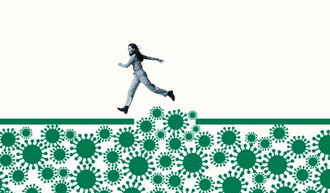 Full length side view of happy young woman jumping over large green coronavirus under ramp against white background