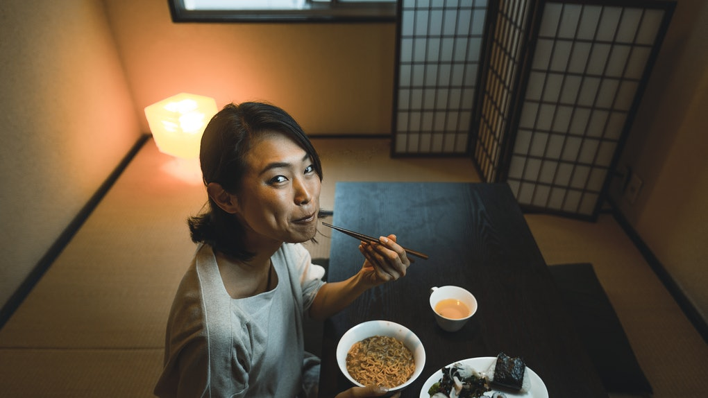 A young woman eats ramen and sushi while sitting at a low table in her home.