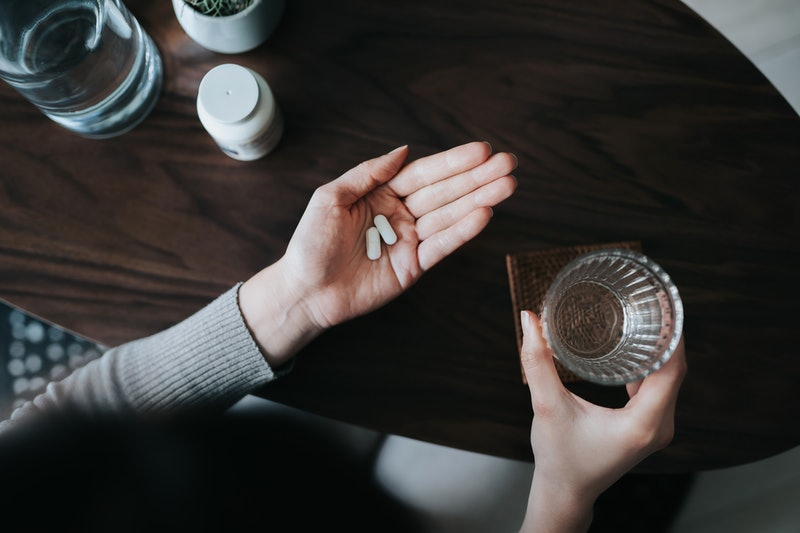 A person holds two painkillers in one open hand, with a glass of water in the other hand. You can safely take ibuprofen or acetaminophen after your COVID vaccine.