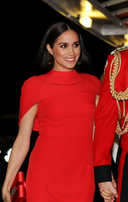 Meghan Markle at an event in a red dress holding her husband, Prince Harry's hand.