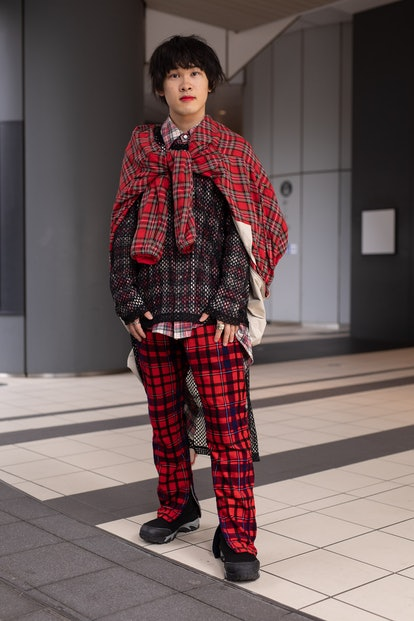 TOKYO, JAPAN - MARCH 20: A guest is seen on the street wearing a red plaid tied jacked, fishnet shir...
