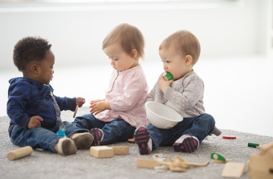 A group of adorable 1-2 year olds sit on a carpet and play with blocks.