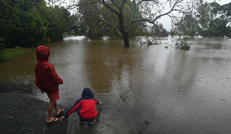 SYDNEY, AUSTRALIA - MARCH 22: Children play in the water at a flooded road in Richmond, north west of Sydney, Monday, March 22, 2021. Thousands of residents are fleeing their homes, schools are shut, and scores of people have been rescued as NSW is hit by once-in-a-generation flooding. (Photo by Steven Saphore/Anadolu Agency via Getty Images)