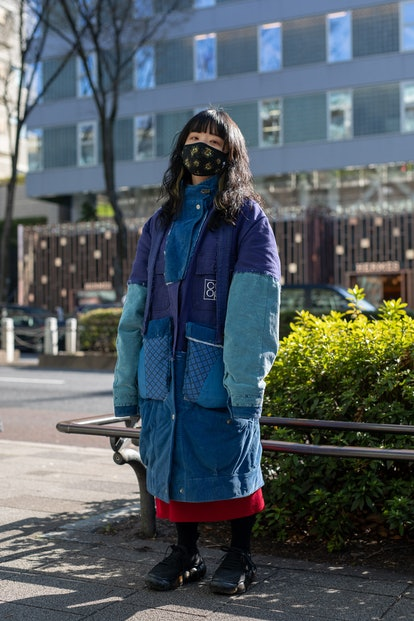TOKYO, JAPAN - MARCH 15: A guest is seen on the street wearing blue Nisai coat, black sneakers, blac...