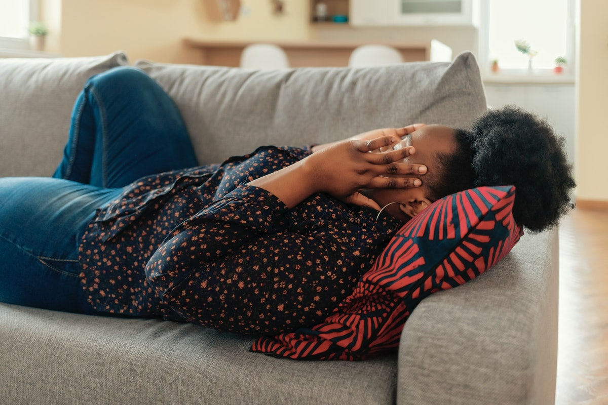 Upset depressed young african american woman lying on couch feeling strong headache migraine, sad ti...
