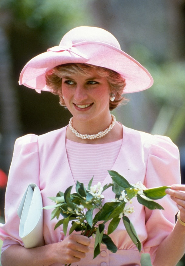 SICILY, ITALY - APRIL 30: Diana, Princess of Wales, wearing a pink dress with puffed sleeves designed by Catherine Walker and a matching hat designed by John Boyd, holds Orange Blossom flowers during a visit to Sicily on April 30, 1985 in Sicily, Italy. (Photo by Anwar Hussein/Getty Images)