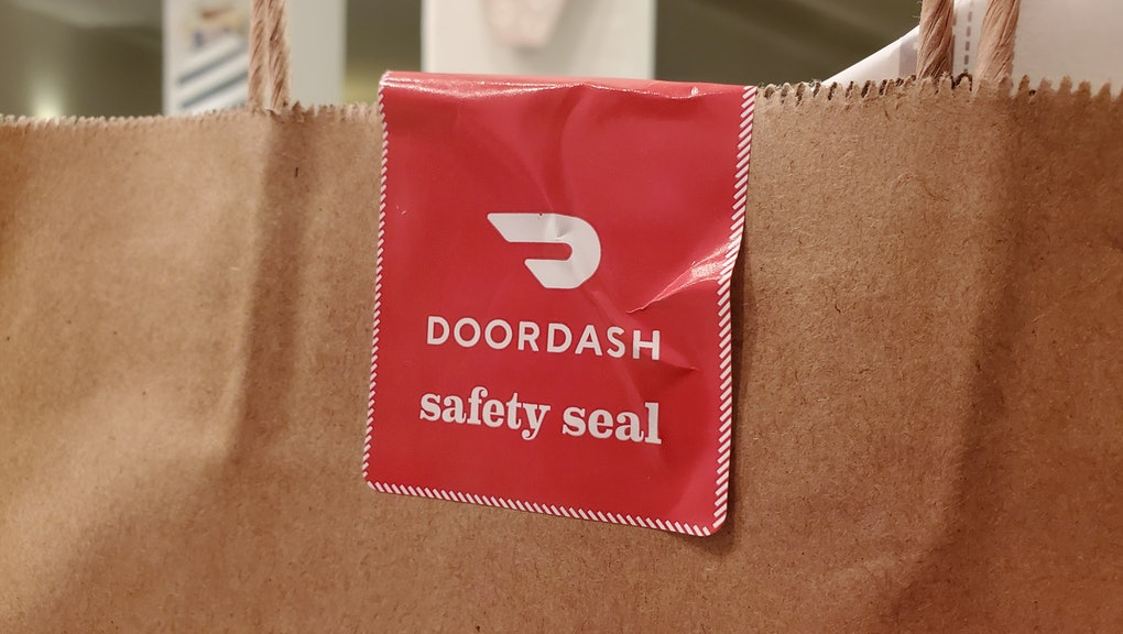 """Close-up of a red and white DoorDash branded """"safety seal"""" attached between the handles of a brown paper bag, photographed in Lafayette, California, February 27, 2021. (Photo by Smith Collection/Gado/Getty Images)"""