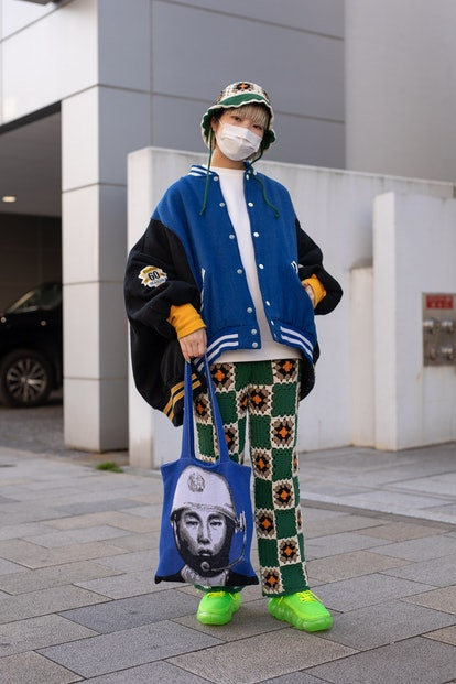 TOKYO, JAPAN - MARCH 15: A guest is seen on the street wearing colorful design knit bucket hat and p...