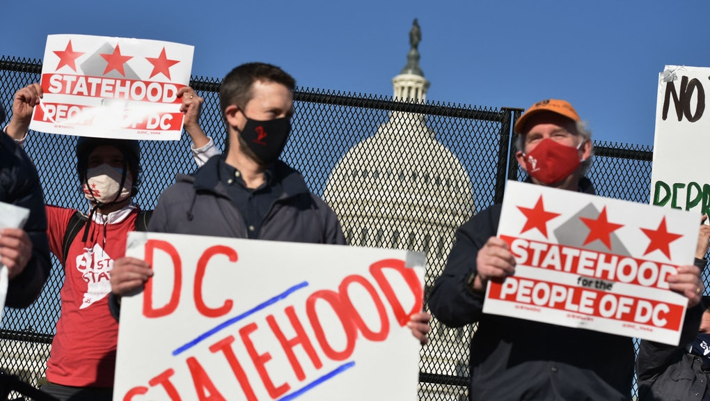 Activists hold signs as they take part in a rally in support of DC statehood near the US Capitol in Washington, DC on March 22, 2021. - Democrats emboldened by their control of the US House, Senate and White House launched a fresh push Monday for statehood for the nation's capital Washington, beginning with a high-profile congressional hearing addressing the issue. (Photo by MANDEL NGAN / AFP) (Photo by MANDEL NGAN/AFP via Getty Images)