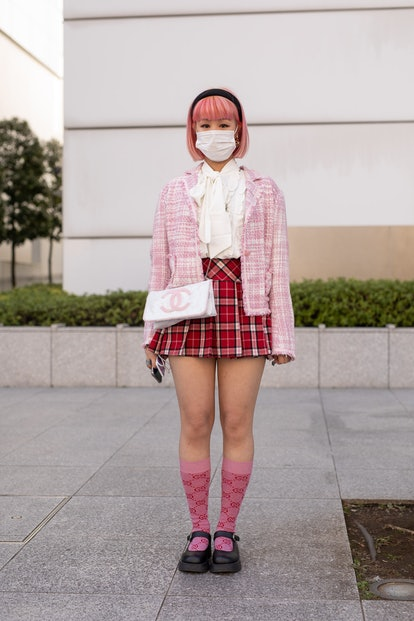 TOKYO, JAPAN - MARCH 15: A guest is seen on the street wearing pink check cardigan, white blouse, re...