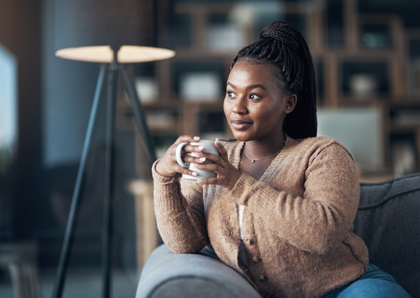 Cropped shot of an attractive young woman sitting alone in her living room and enjoying a cup of coffee