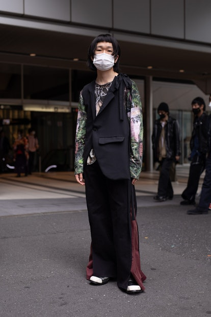 TOKYO, JAPAN - MARCH 20: A guest is seen on the street wearing a colorful design shirt, black vest, ...