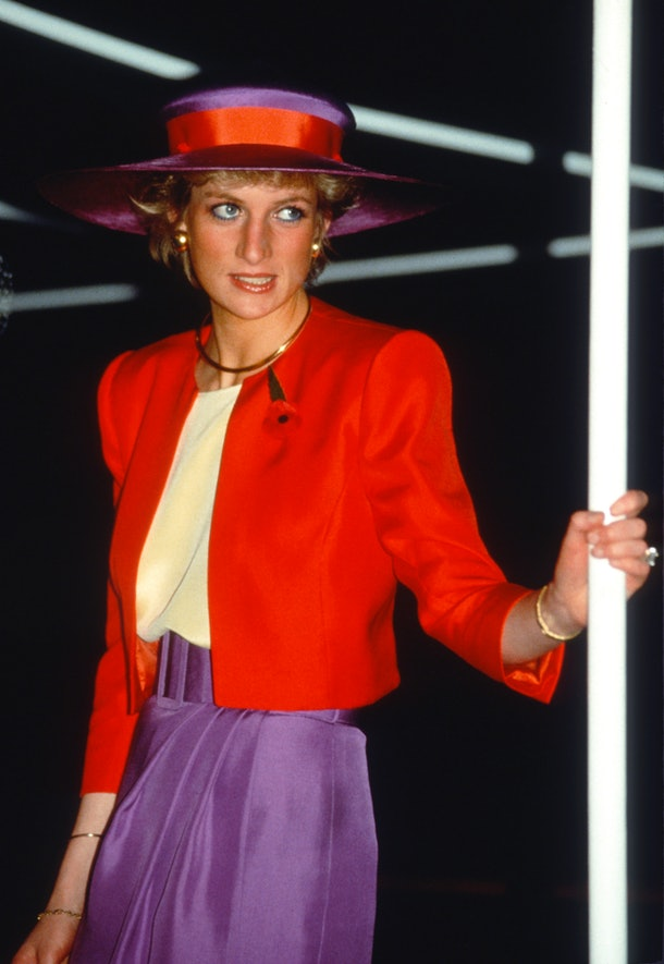 HONG KONG, CHINA - NOVEMBER 07: Diana, Princess of Wales, wearing a red and purple suit designed by Catherine Walker with a matching hat and remembrance poppy, arrives on the Governor's launch on November 7, 1989 in Hong Kong, China. (Photo by Anwar Hussein/Getty Images)