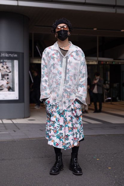 TOKYO, JAPAN - MARCH 20: A guest is seen on the street wearing a shear shirt, floral print robe, bla...