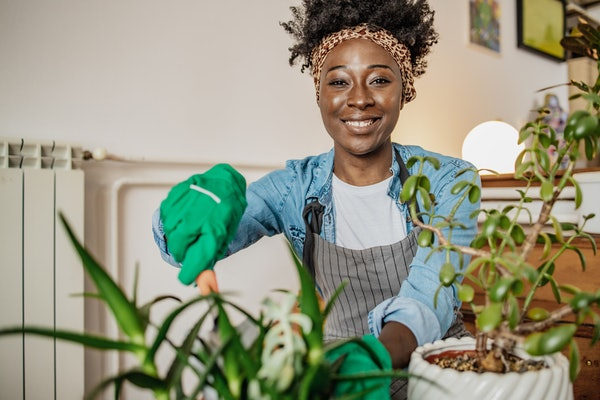 African woman taking care of plants at her home, she is holding a plant and smiling