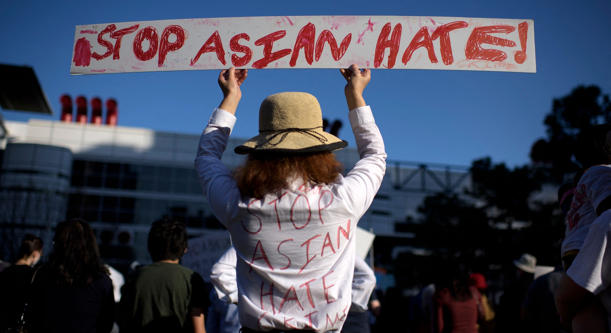 TOPSHOT - Sally Sha holds up a sign during a Stop Asian Hate rally at Discovery Green in downtown Houston, Texas on March 20, 2021. (Photo by Mark Felix / AFP) (Photo by MARK FELIX/AFP /AFP via Getty Images)