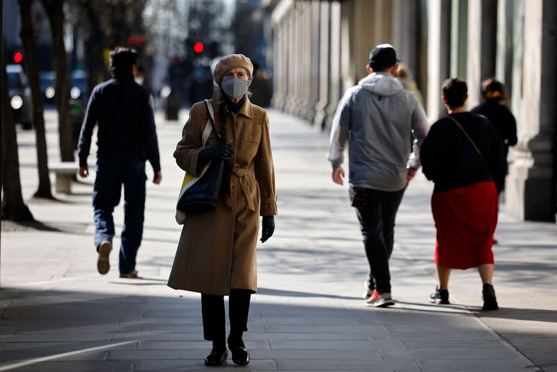 "A pedestrian wearing a face covering walks along a quiet Oxford Street in central London on March 22, 2021. - Britain will on March 23, 2021, mark the one-year anniversary of the first coronavirus lockdown with a ""National Day of Reflection"", which will see parliament hold a minute's silence in tribute to the more than 125,000 people who have died. (Photo by Tolga Akmen / AFP) (Photo by TOLGA AKMEN/AFP via Getty Images)"