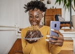 An African-American woman is celebrating a birthday on a video call, she is holding a birthday cake ...