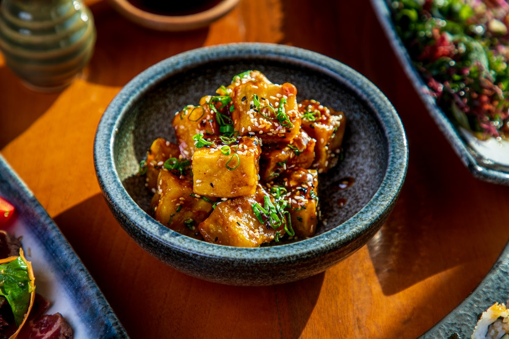 Tofu cubes serving in a bowl, seasoned with black and white sesame and chopped scallion